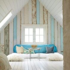 Pale blue and white paneled walls create a rustic, beach cottage vibe in this attic retreat.