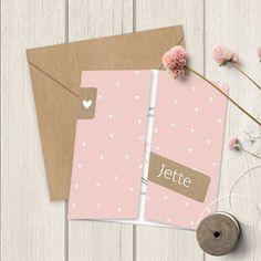 Geboortekaartje met aan de voorkant 2 luikjes die vanuit het midden opengaan. Klein labeltje met hartje en een label met de naam. De achtergrond is roze met witte hartjes. Aan de binnenkant zijn de hartjes roze.