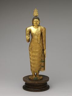 """Sri Lanka, 18th C. Kandyan-period (1480-1815) style at its best. The Buddha's physique is robust and the face is full. His robe appears to ripple. Lakshana - auspicious marks trace the palm of his raised hand and the left arm is straight, a convention in the latter period. Copper Alloy. 25.5"""" H."""
