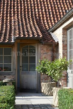 The simple entrance to the restored farmhouse detailing the mellow brickwork and terracotta tiled roof