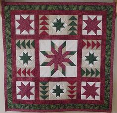 """Quilts:  This is a wall hanging I made for my son when he bought his new house.  I used burgundy, hunter green, taupe, and white-on-white as the background fabric for the stars.  The center star  is a 12"""" paper pieced block.  The corner stars are 6"""" blocks and the green stars are 4"""" blocks.  Also used in this wall hanging is flying geese blocks around each green 4"""" star.  I really enjoyed working on this project.  I thought it came together rather nicely."""