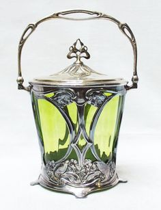 Very nice cookie jar. Art Nouveau Light green glass in pewter and brass frame. WMF, Germany early Height pot 14 cm With handle 24 cm Diameter cm Silvering of lid should be redone (see photo) Wmf, Cookie Jars, China Porcelain, Framed Art, Art Nouveau, Glass Art, Candle Holders, Metal, Vases
