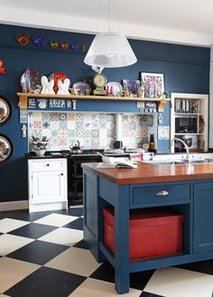 This family kitchen reflects its artist owner's creativity. Bespoke Shaker-style furniture and Iroko wood worktop by David L Douglas. Cabinetry in Pointing and Hague Blue estate eggshell by Farrow & Ball. For a similar splashback, try Patchwork tiles by Emery et Cie.