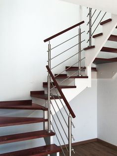 Residential stainless steel round bar railing and wood rail solution by Indital