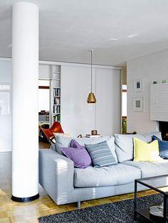 Olohuone on keskellä kotia. Keittiö jää takan taakse ja ruokatila on avoin sekä keittiöön että olohuoneeseen päin.