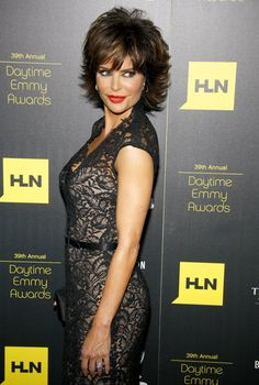 Lisa Rinna has worn various versions of her signature shag for years but this latest version is big and sexy.  The top is tousled, full, and cut in layers that help with the lift. There is no part and a full bang. The back is longer down to shoulder length and is cut in graduated lengths. The ends are flipped up and out for a full of volume appeal. The color is medium brown with honey highlights. To help with styling turn head upside down and blow dry to remove a good amount of moisture. ...