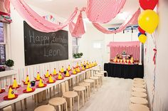 I love this table setting: everyone has a party hat, and we can probably put the clown nose on top of the hat, so silliness for all!  Also love the drapes from ceiling, clean, simple, and pretty!