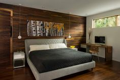 With a wood accent wall, wood floors and woodsy artwork, this contemporary bedroom boasts a strong connection to the outdoors. The rich tones of wood give the space an unparalleled warmth, which is balanced with a cool gray bed and charcoal bedding.