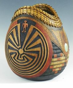 """""""Man in the Maze"""" - An extraordinary gourd with a woodburning, pine needle coiling, caving. Adorned with turquoise. 8-1/2"""" tall x 7"""" diameter. Artist: Judy Richie."""