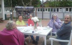 Kakkukahvilan väkeä nauttimassa yhteisestä hetkestä kahvin ja leivosten parissa