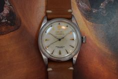 This vintage 1954 Rolex Oyster Perpetual, Ref. 6284, features the classic and unusual 'honeycomb' or 'waffle' textured dial with applied gold arrow markers, Rolex crown and logo, and alpha hands. This simple time-only watch with center sweep seconds sports a smooth bezel and a stainless steel, semi-bubbleback case. This model is aesthetically similar to the watch provided by Rolex to Sir Edmund Hillary for his Everest expedition (Store Inventory# 9888, listed at $3250).