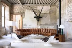 Michael Perry's Home photographed by Jean-Francois Jaussaud. Light coloured stone walls are set as a nice backdrop to the $50,000 sofa: The Endless Sofa by de Sede.