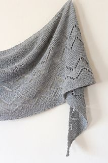 Jindabyne is a garter stitch crescent shawl featuring a chevron lace stitch pattern. The shawl was created using Alpaca 4 ply, a soft and rustic alpaca fingering yarn, from Adagio Mills.