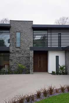 Designed by David James Architects in Dorset, England. The blend of stone, render, glass and aluminium making up the street facade creates visual contrasts with the iroko timber gate.