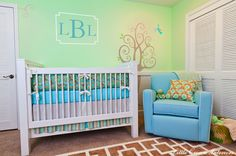 Adorable green & blue gender neutral nursery design with green walls paint color, white crib, brown geometric chain link Labyrinth Kids Rug, Monaco Adult Glider in azure with white piping, chocolate brown turquoise blue teal crib bedding, chair rail and tree mural. (source: Little Crown Interiors)