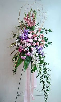 Feminine bent easel arrangement-spray featuring roses, snapdragons, stock, dianthus and dendrobium orchids with camellia foliage, ti leaves and Italian.