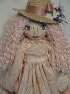 She is a beautiful hand made art doll.   This hand made doll measures 26 inches tall.   Her body and face are made from premium muslin fabrics.   She has a hand painted face, her nose is needle sculptured.   The hair is a soft peach color, made from yarn.   Her hair is all hand sewn on.   She is dressed in a soft peach colored dress in a floral design.   A pair of bloomers is made from a peach colored cotton fabric.   Her high heeled shoes are painted a soft green color.   The stockings are…