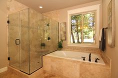 Intricate tile details inside this luxurious glass-walled shower continue above the soaking tub. The MacArthur by Stone Bridge Homes NW.  Lake Oswego, OR