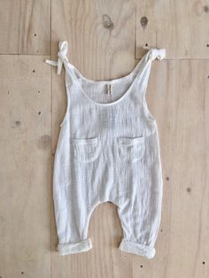 Runaway overalls in white lightweight jumpsuit in white cotton gauze. shoulder ties to adjust fit and front pocket details. please note. sizes run small, we suggest that you go up a size. also available now in cream stripe