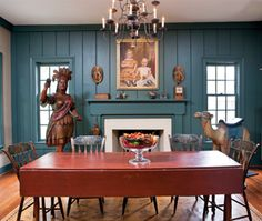 Painted fancy chairs are set around the original red-painted, circa-1820–1840 harvest table, which dealer Marguerite Riordon used in the dining room of her home. The circa-1840–1860 portrait of two young boys hangs above the mantel, on which there is a paint-decorated box, Schimmel eaglet, and carved dog and pigeon. The carver of the Indian trade figure worked for Samuel Robb (1851–1928), whose influence is evident in the treatment of the feathers, the forward motion of the arm, and the…