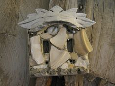 Mosaic double switch plate in white with a chunk of wood across the top.