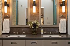 The custom-designed vanity features clean lines and inset handles. The soft gray front is paired with charcoal countertops, while the reclaimed wood backsplash is highlighted by oil-rubbed bronze sconces and custom mirrors.