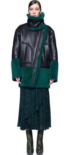 Shearling jacket bicolor from Kenzo. Cute, warm, fashion all these attribute are mixed together in a modern way. High and large collar, large pockets aside, cuffs in fur, zipper aside, ripples behind creating a beautiful movement, two buttons on the neck....what else?? Black leather and green in contrast, in a really warm jacket!