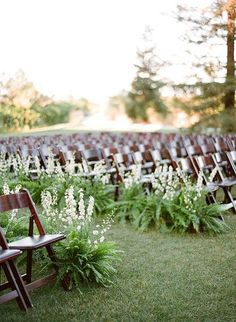 Create an earthy, woodland vibe by lining the aisle with emerald-green ferns combined with white delphiniums | Brides.com