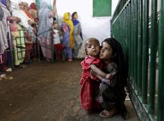 Pakistani Abla Zahir, 6, holds her brother Yaseen, 1, while waiting to receive a ration of rice during a donated food distribution at the Beri Iman, a shrine of famous Sufi Saint Beri Imam, in Islamabad, May 4, 2012.
