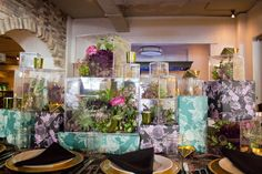<p> Flower and succulent arrangements in clear boxes sat atop deep teal and purple floral-wrapped boxes to form what designer...