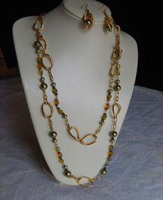 Collar largo elaborado con cubos de cristal, gotas de cristal y ganchos en baño de oro.