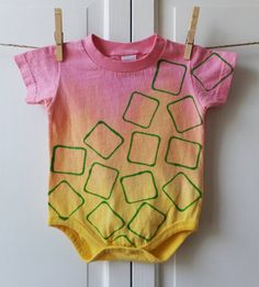 Size 12 month Bodysuit in a pink, tangerine and sun yellow ombre with a stamped kelly green block pattern.    Hand dyed and hand stamped with Pro MX