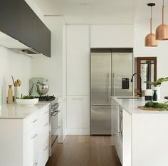Great small kitchen idea, white with orange accent lights www.remodelworks.com