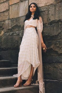 Ivory and gold brocade dhoti skirt with leather crop top & net embroidered cape. Estimated shipping: weeksCare instructions: Dry clean only Dress Indian Style, Indian Fashion Dresses, Indian Gowns, Indian Designer Outfits, Indian Attire, Indian Wear, Fashion Outfits, Ethnic Fashion, Fashion Fall