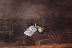 Stamped rustic tab and Turquoise duo hang from a delicate chain of blackened sterling silver.Tab 1""