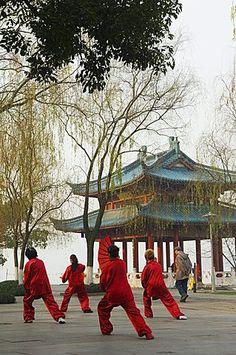Women practising tai chi in front of a pavilion on West Lake, Hangzhou, Zhejiang Province, China