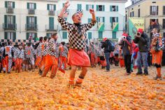 An orange fighter happily cheers at the end of the Battle of the Oranges, a medieval revolts reenactment at Ivrea's Carnival, Italy