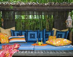 To connect the inside with the outside, Moises Esquenazi created a series of living areas in his Los Angeles backyard, including this cabana with a daybed that echoes the colors he used in the interior of his bungalow. The natural fiber pillows and the blue squares are from RL Home; striped and print pillows are by Trina Turk