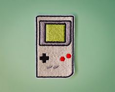Oh how we miss the shades of green, right?? Wear this Nintendo Gameboy patch with pride! The iron-on adhesive backing makes this patch a great