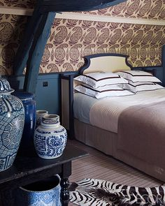 In the master bedroom of a Normandy home, the walls are covered in a Jasper hemp.