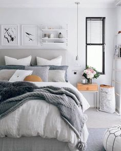 Use of fabric headboard in light gray/ sand. with gray and white bedding.