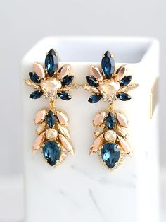 Blue Navy Earrings, Bridal Blue Navy Earrings, Dark Blue Chandeliers, Blue Rose Gold Earrings, Champagne Blue Earrings, Blue Long Earrings Petite delights original design Petite Delights is an Official SWAROVSKI® Branding Partner Made with real genuine high quality Austrian Swarovski ©Crystal and settings . Our brand is legally licensed & authorized By Swarovski Company for high quality manufacturing. This pair comes with Swarovski genuine tag , this is unique to our store . They serve as...