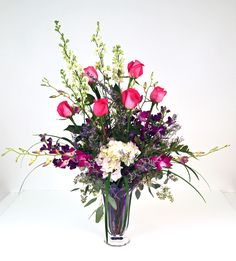 Enchanted Romance Gillespie Florists - Indianapolis IN The Enchanted Romance bouquet is an art glass vase filled with delicate dendrobium orchids, large white hydrangea, pretty pink long stem roses, white larkspur, limonium, seeded eucalyptus and bears grass!