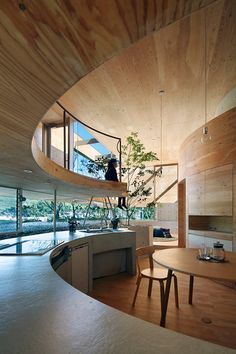 Curving levels house the bedrooms, kitchen etc while the whole space is bordered by a rock garden and indoor trees, the structure itself comprised of wood stretching from floor to ceiling. Pit House-Stilts-04