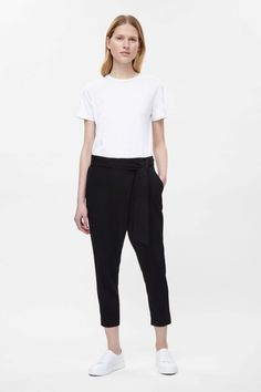 These cropped trousers have a wrap-over front with a detachable tie-fastening belt. Designed to sit on the waist, they have slanted pockets, tapered legs and a zip fly fastening.