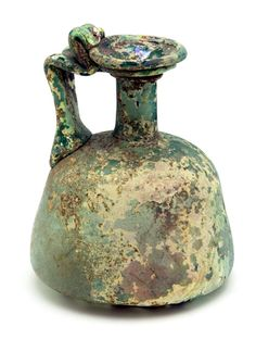 "Colorful Squat Jug. Roman, 3rd to 4th century AD. Height: 6"". Blown in fairly colorful green glass this jug has a shallow funnel mouth with carinated rim, cylinder neck, and a rounded conical, bell-like body. With indented bottom. A ridged and folded handle is attached to thick and thin rings of glass beneath the mouth. $1,006"