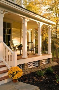 Love the lattice between stone columns underneath and the wood stained floor with white columns and railings