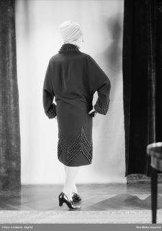 Kvinnlig modell iklädd kappa och turbanliknande hatt. Bakifrån. Fotograf   Sigrid Lenkert 0ed06fb4a9899