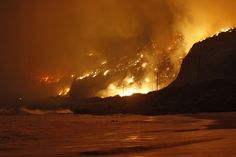 """IMPACT: """"The Springs Fire rages along the Pacific Ocean north of the Ventura County Line May 2, 2013. A wind-driven wildfire raging along the California coast north of Los Angeles prompted the evacuation of hundreds of homes and a university campus on Thursday as flames engulfed several farm buildings and recreational vehicles near threatened neighborhoods. """""""