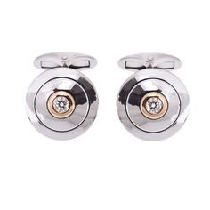 18ct White and Yellow Diamond Cufflinks  This pair of circular 18ct white gold boss motif cufflinks inserted at their centre with a hint of yellow gold encircling a single brilliant cut diamond.
